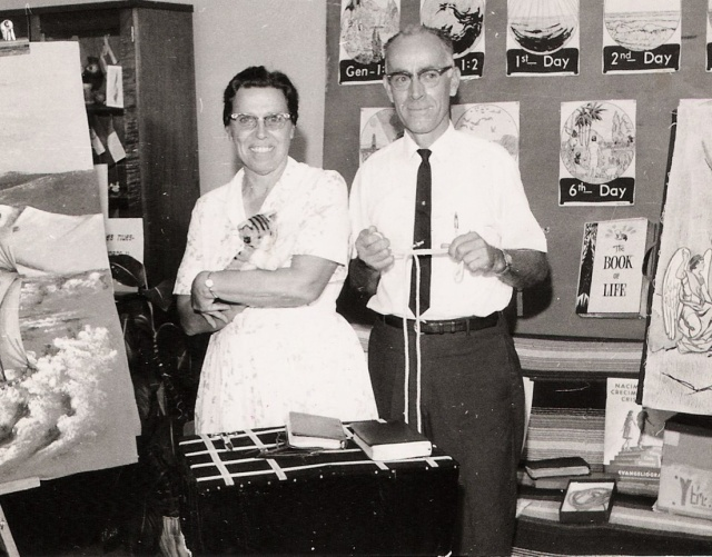 Pearl and Howard Wolgemuth stand in the center of a small display area. Pearl is holding a hand puppet shaped like a cat. Behind them are various images of Bible scenes as well as a flannelgraph board.